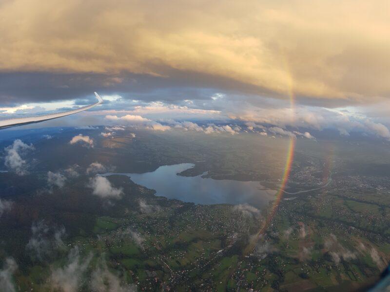 Zdjęcie tęczy pod chmurą nad Jeziorem Żywieckim.